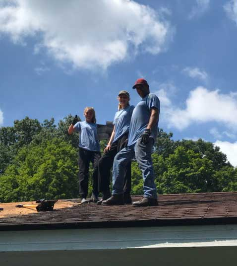 Emily, Lara and David Snyder working on the roof