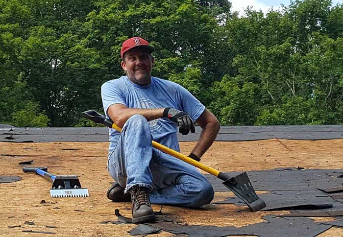 David Snyder takes a break from ripping off the old roof materials.