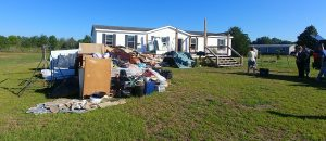 Flood-damaged belongings piled outside in preparation for repairs.